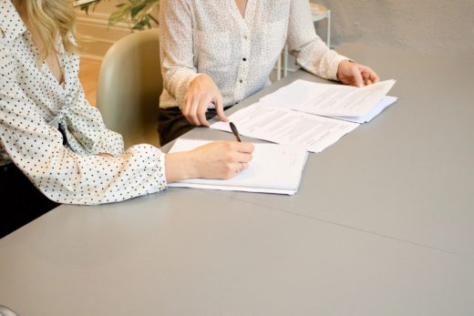 two people signing contracts