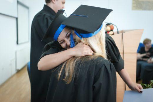 Students at a graduation, hugging.
